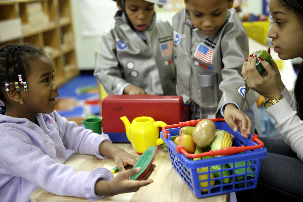 Oumou Balde, 4, left, plays with her teacher Jacqualine Sanchez, right, and some pretend food in a pre-kindergarten class at the Sheltering Arms Learning Center in New York in a program to educate children about nutrition and health. A new study published in the New England Journal of Medicine on Wednesday finds that much of a child's