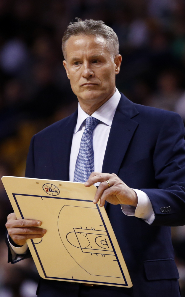 76ers Coach Brett Brown, a South Portland native, holds a clipboard during a timeout Wednesday night at Boston.