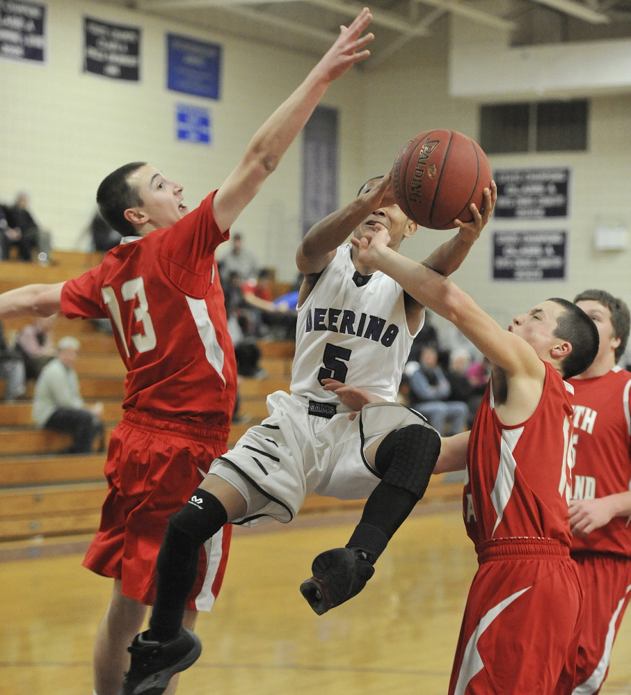 Chhorda Chhorn of Deering finds room to drive between Jack Fiorini, left, and Patrick Conley of South Portland during Deering's 63-53 victory Thursday night. The Rams improved to 11-5 and dropped the Red Riots to 6-9.
