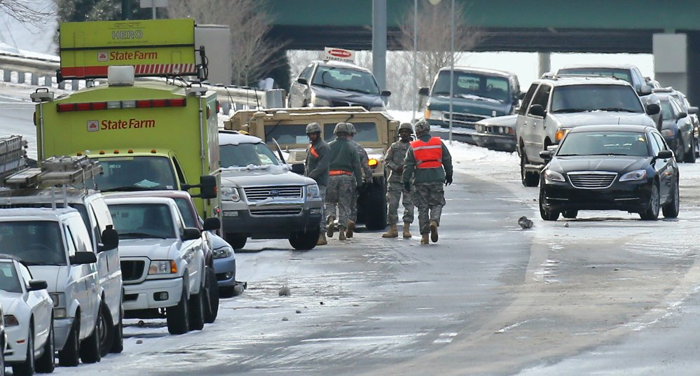 Georgia National Guard troops in humvees check on stranded motorists and search abandoned vehicles to give aid to those still stuck on the highway at Roswell Road and I-285 on Wednesday afternoon.