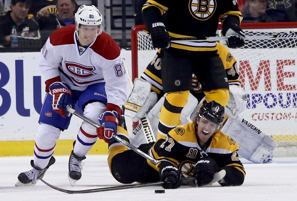 Boston Bruins' Dougie Hamilton dives on the ice to clear the puck ahead of Montreal Canadiens center Lars Eller during the second period Thursday in Boston.