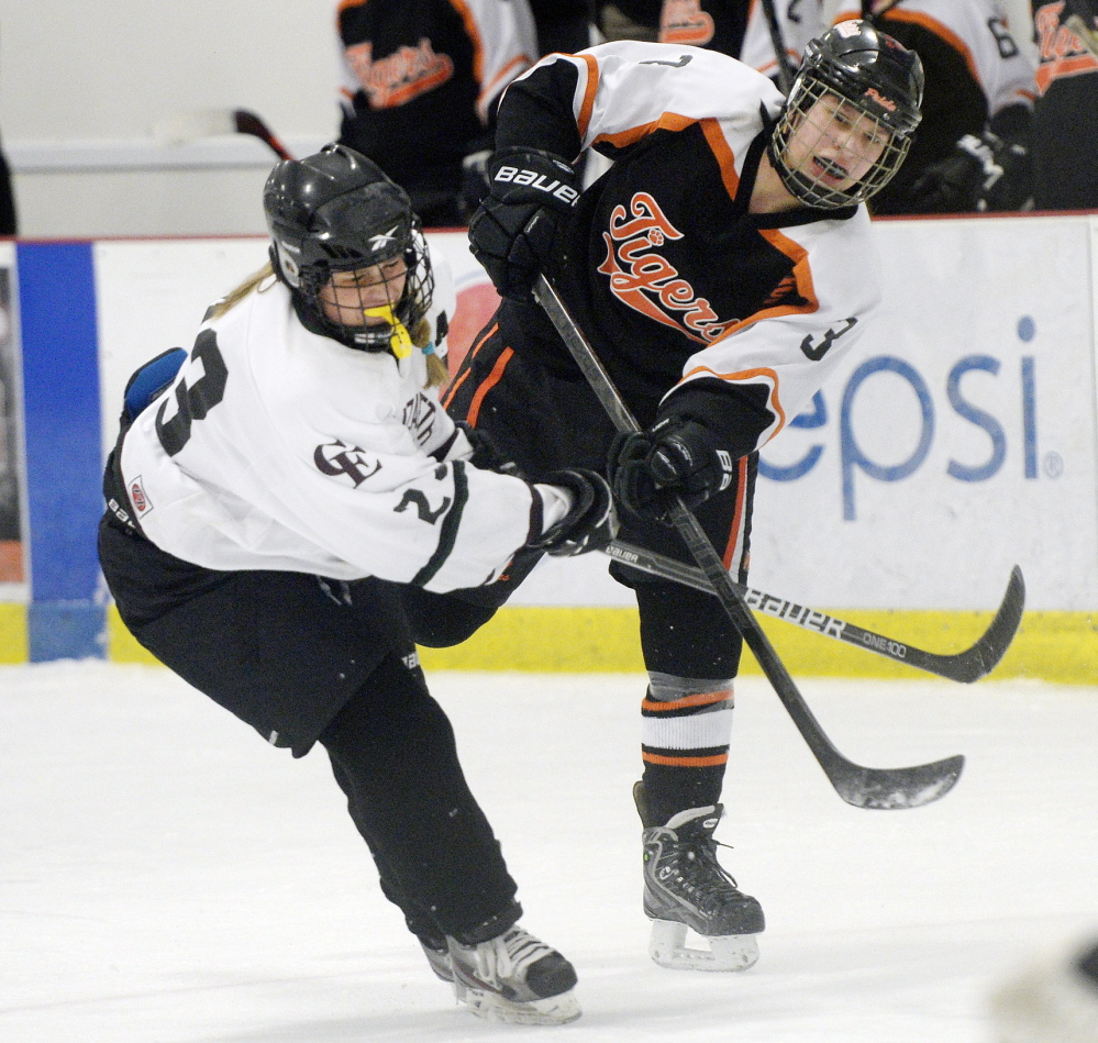 Brea Rivard of Biddeford takes a shot on net Thursday as Casey Murray of Cape Elizabeth/Waynflete attempts to break up the play. Biddeford scored three times in the third period for a 3-1 victory.