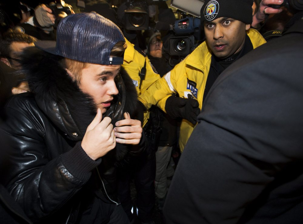 Canadian musician Justin Bieber is swarmed by media and police officers as he turns himself in to city police for an expected assault charge, in Toronto, on Wednesday.