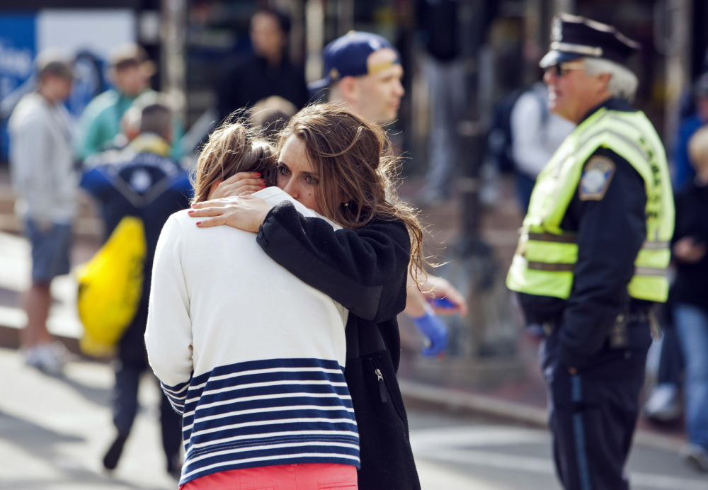 A woman comforts another after explosions interrupted the 117th Boston Marathon April 15, 2013. Legal experts say a suspect in the bombing might benefit from a trial held in Boston, where opposition to the death penalty, which he faces, runs high.