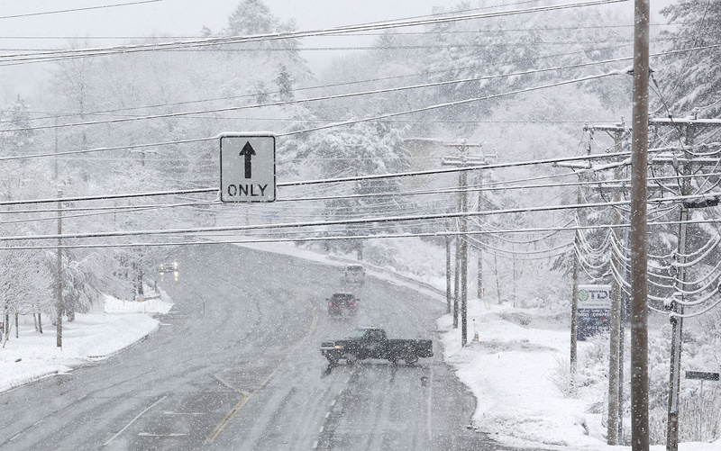 Heavy snow continues to fall and collect on tree branches and power lines on Sunday along Route 1 in Scarborough.