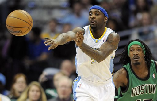 Denver Nuggets guard Ty Lawson passes the ball while being defended by Boston Celtics forward Gerald Wallace in the first half of Tuesday's NBA game.