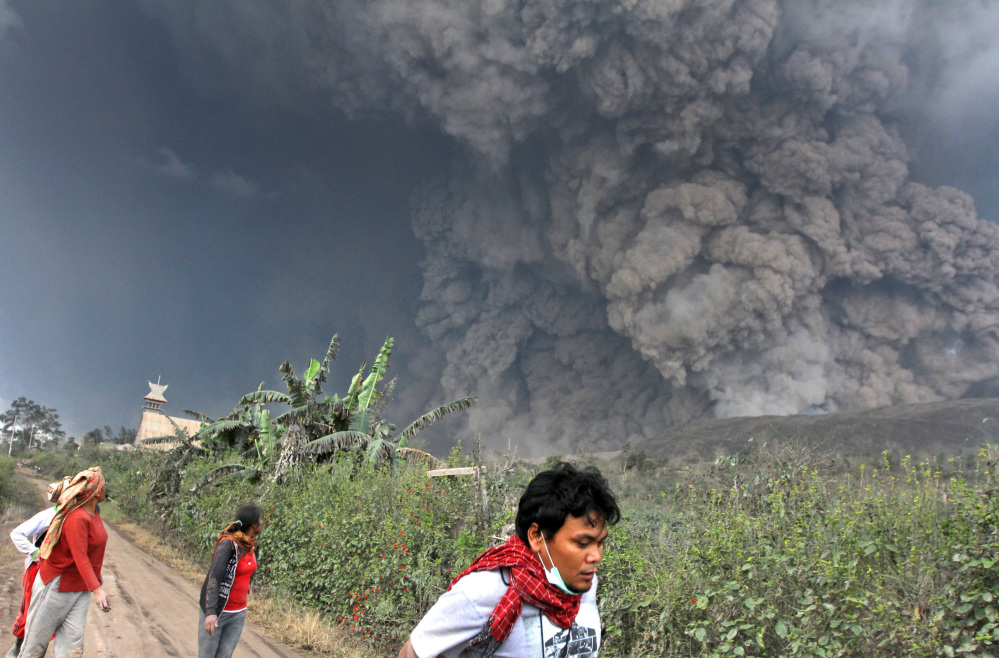 Villagers and a journalist flee as Mount Sinabung, which has been rumbling for four months, erupts in Indonesia, Saturday. Some 14,000 people had just returned to the area, because the volcano had seemed less active.
