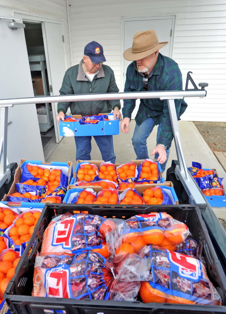 Dave Dawson, right, and Kerry Temple with the Waterville Area Food Bank unload cases of oranges at the United Methodist Church on Pleasant Street in Waterville on Friday.