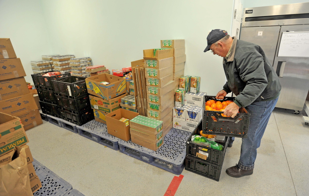 Kerry Temple, a volunteer with the Waterville Area Food Bank, delivers goods to the United Methodist Church on Pleasant Street in Waterville on Friday.