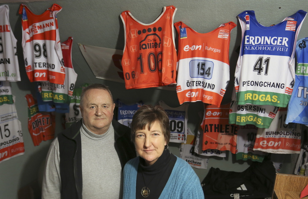Chris and Debbie Currier pose in their home in front of bibs worn throughout the years by their son. In another room, Russell Currier's medals hang from the arm of an exercise machine. The biathlete headed for the Olympics in Sochi, Russia, is markedly modest about his successes.