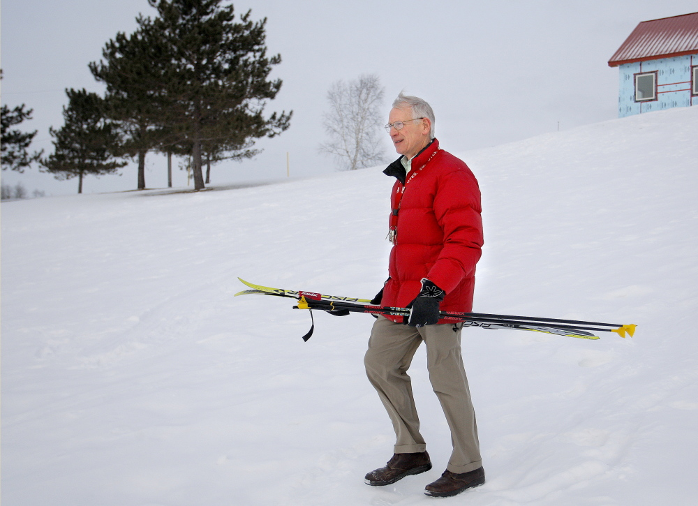 """Bob Sprague, a retired ski coach and teacher in Caribou, walks near trails where he used to help train Russell Currier. """"You watched him and you knew,"""" he said of Currier."""