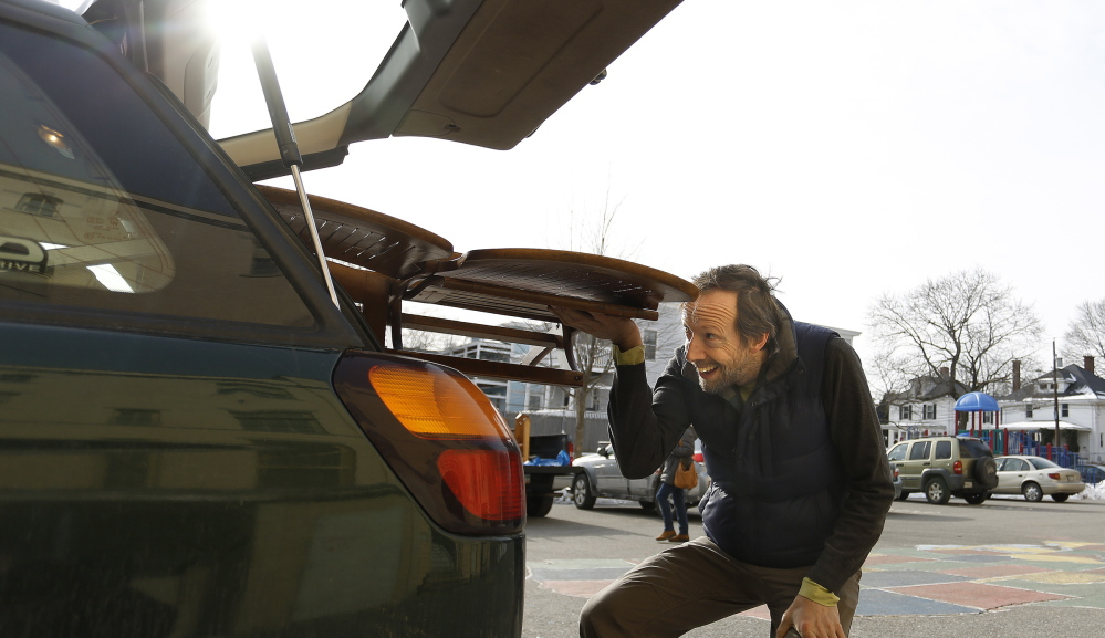 David Siegfried of South Portland tries to cram a set of wooden chairs into the back of his Subaru after scouring the Nathan Clifford School for furniture Saturday.