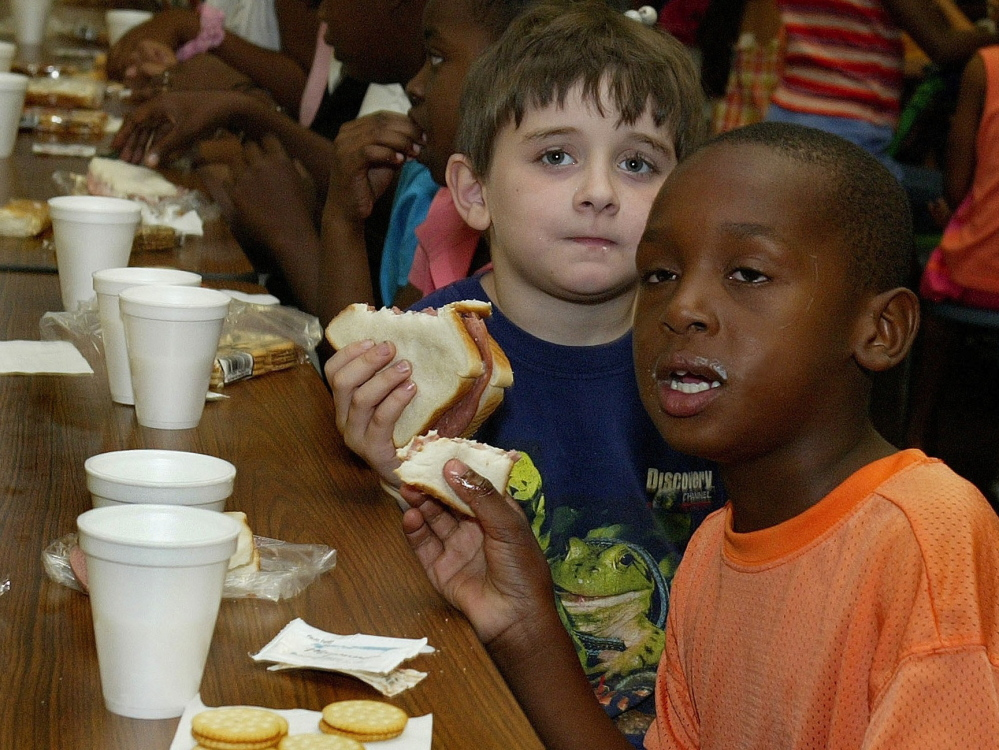 Dyquan Gordon, 7, right, and Bradley Cremer, 6, sit down for lunch provided by a federally funded summer program at the Boys & Girls Club in Apalachicola, Fla., in June 2004. Some 85,000 Maine children qualify for assistance paying for lunch during the school year, but only about 13,000 of them currently receive meals in the summer.