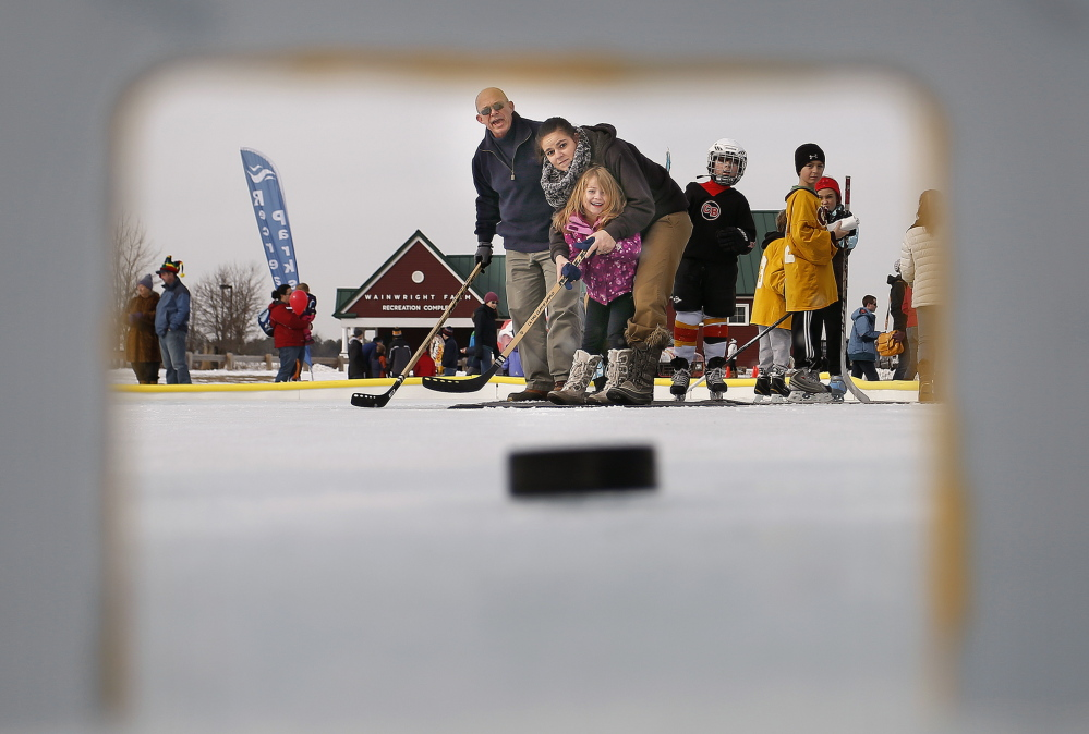 """Tom Meyers, left center, cheers as Cyndi Ouellette and her daughter, LilyAnn Wood, 4, watch as their shot speeds toward the goal while playing """"Score-o"""" at WinterFest."""