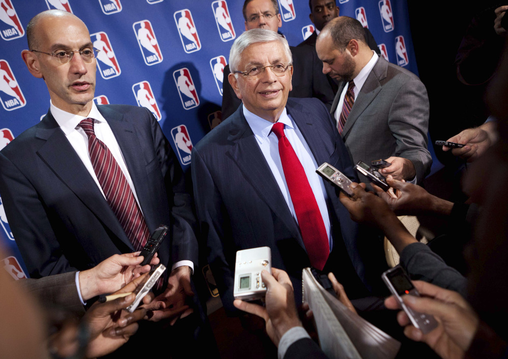 David Stern, center, speaks to the news media alongside Adam Silver in this November 2011 photo. Silver takes over as NBA commissioner from Stern, who retired after 30 years in his position.