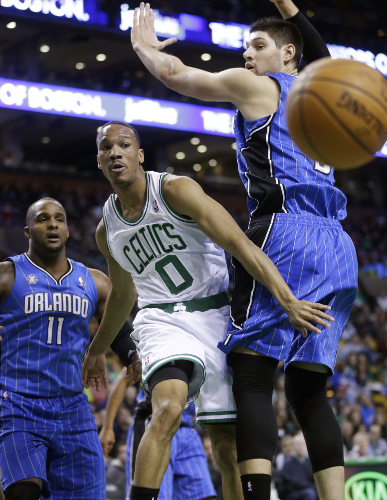 Boston Celtics guard Avery Bradley (0) vies for a loose ball with Orlando Magic forward Glen Davis (11) and center Nikola Vucevic, of Montenegro, right, in the first quarter of an NBA basketball game Sunday, in Boston.
