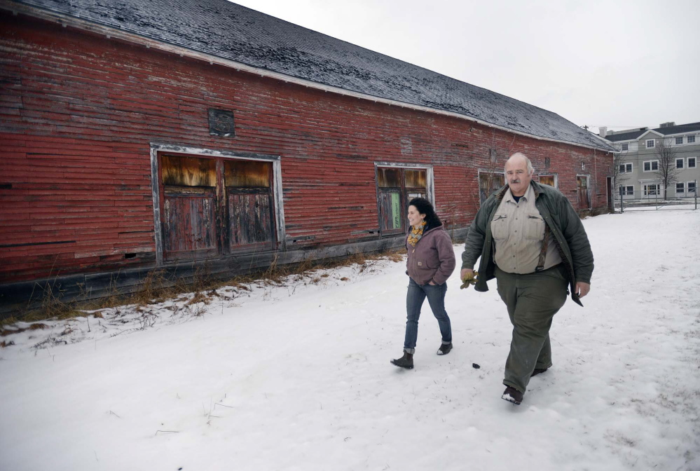 Maina Handmaker and Gary Brooks walk past the barns where they hope to see a permanent farmers market in Brunswick. A feasibility study estimates that it would cost about $1.7 million to revamp the freight sheds, owned by Brooks, and make other improvements.