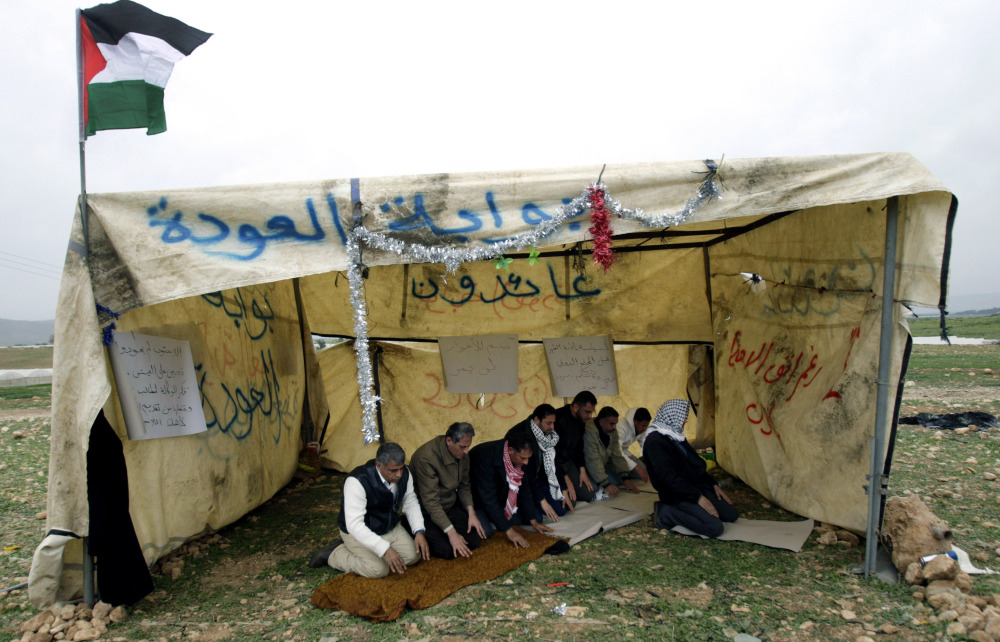 Palestinian activists pray Sunday inside a tent they built in Jordan valley near the West Bank town of Tubas.