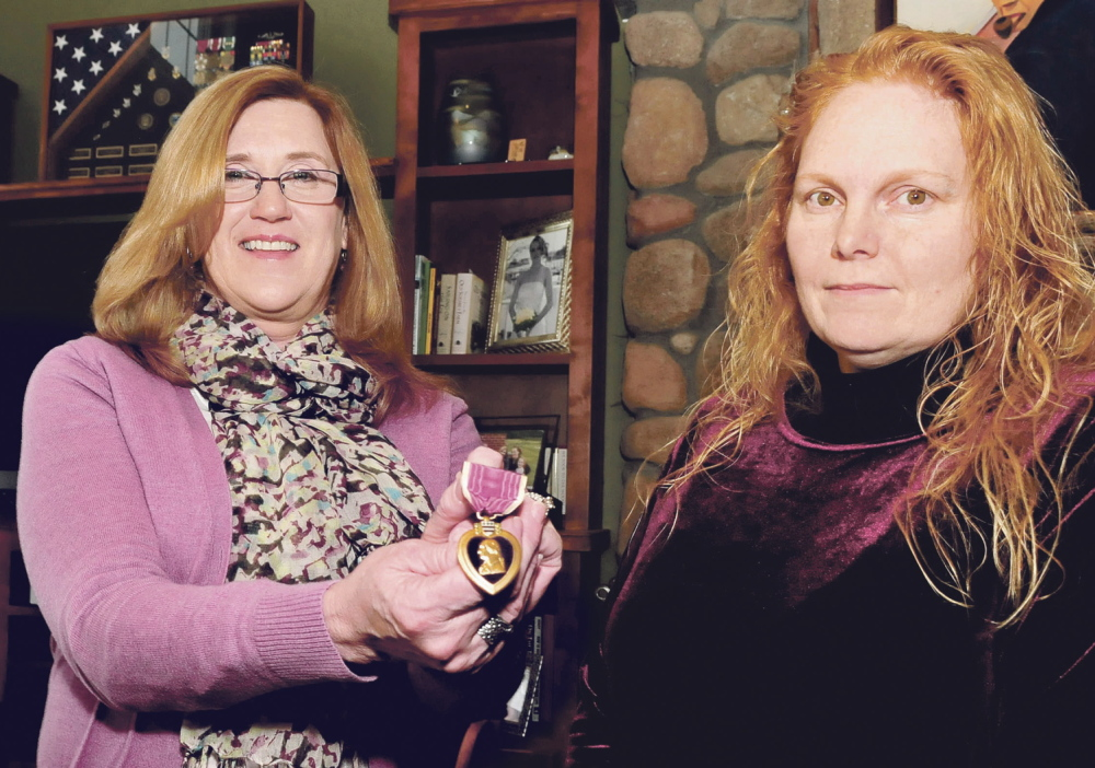 """Monica Pollard, left, holds the Purple Heart that was given to her by Sheila Bedi of Vershire, Vt., right, on Sunday. """"I am happy and honored to take care of it,"""" Pollard said."""