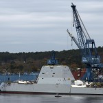 A security boat is dwarfed by a Zumwalt destroyer at Bath Iron Works in 2013.