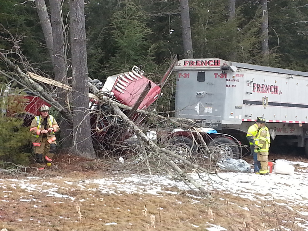 Emergency personnel examine the scene of a tractor-trailer crash on the Maine Turnpike on Monday morning.