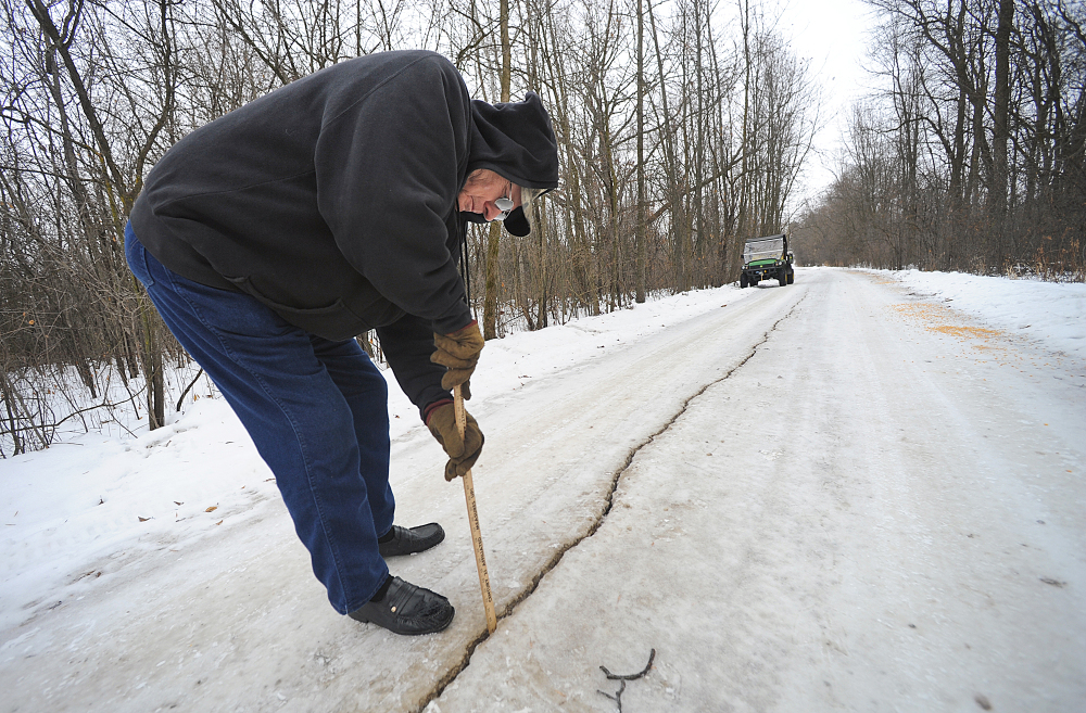 Dennis Olsen measures a fissure that he said was about an inch wide and at least 8 to 10 inches deep in his rural driveway following a frost quake in Waupun, Wis., last month.