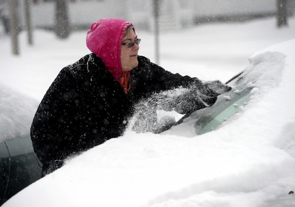 Lori Raftis of Saco clears snow off her car during Wednesday's snowstorm.