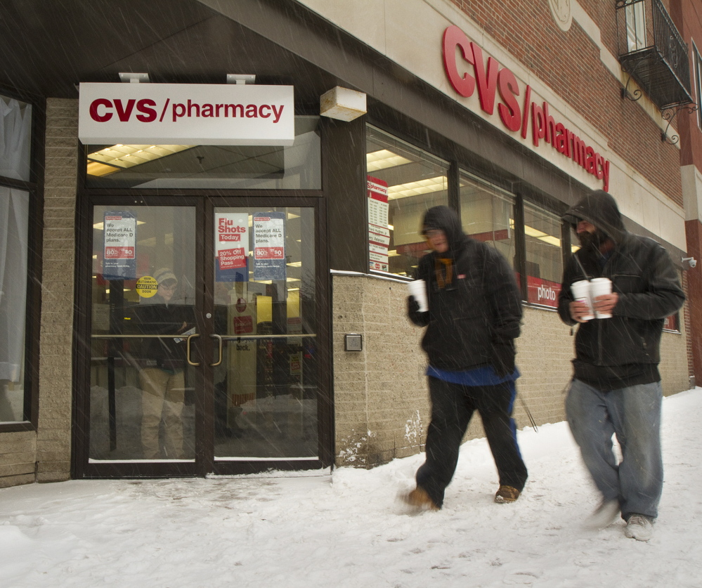 Pedestrians pass the CVS on Congress Street in Portland on Wednesday, the day the national chain announced it will stop selling tobacco products in its 7,600 drugstores.