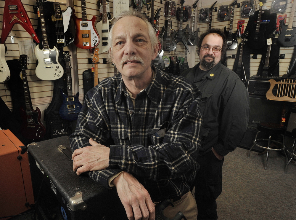 Mike Fink, owner of the Guitar Grave, has posted about 40 videos of pawn shop activities online. His employee, Mark Belanger, right, edits the video.