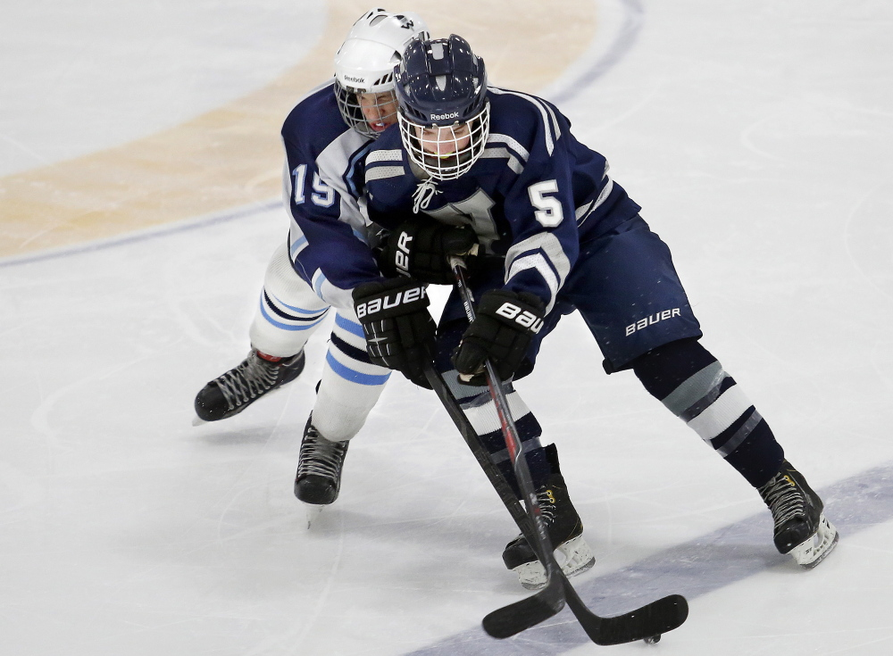 John Tibbetts, left, of Westbrook tries to take the puck away from Yarmouth's Chris Romano during Thursday's game at USM Ice Arena in Gorham. Yarmouth won, 10-1.