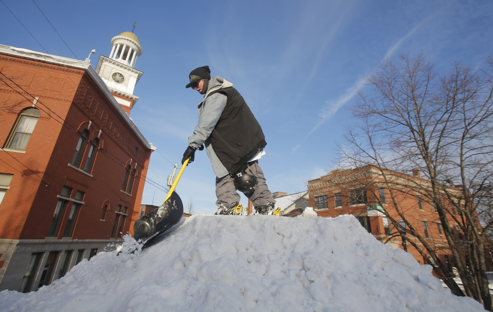 Gregory Rec/Staff Photographer Jon Steltzer shovels snow from a mound of snow outside Biddeford's City Hall on Thursday in preparation for the Big Air competition and WinterFest, which starts Friday night and runs through the weekend.
