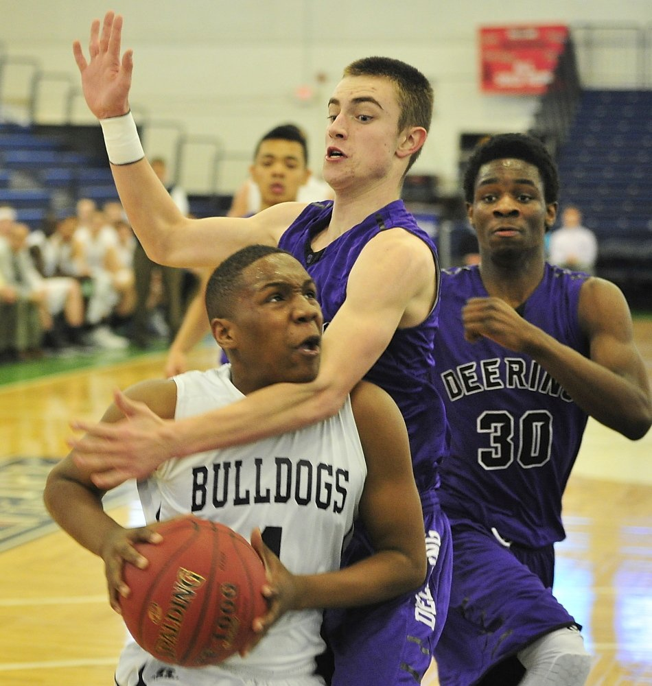 Amir Moss of Portland gets fouled by Deering's Jacob Coon as Benedict Williams looks on during a regular-season finale Thursday at the Portland Expo. The Bulldogs finished their first undefeated regular season in 15 years, winning 63-46.