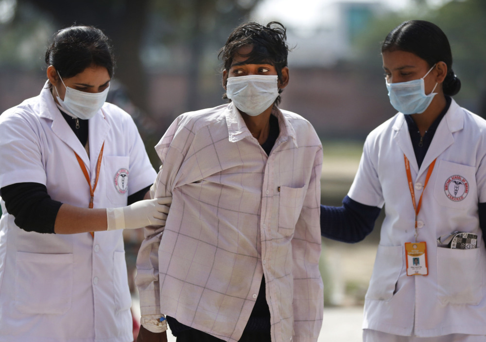 Nurses help a tuberculosis patient, center, walk to a government hospital at Ram Nagar in Varanasi, India, on Monday. TB rates are high among sari weavers. Photo/Rajesh Kumar Singh)