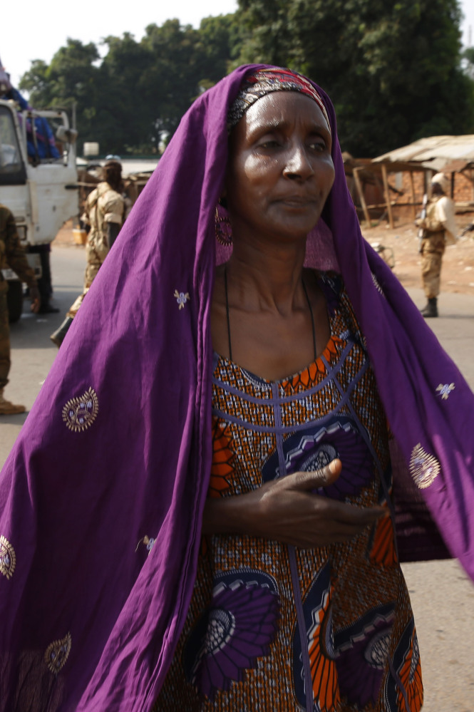 A Muslim woman hurries to join the exodus from the capital of Central African Republic on Friday.