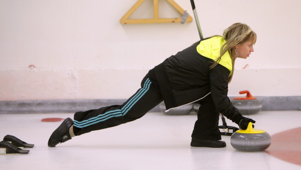 """Erica Sprague of Lincolnville releases a curling stone while competing at the Belfast Curling Club. Players say the game is more like chess than shuffleboard and bowling. """"We bristle and stiffen at the words 'shuffleboard' and 'bowling,' """" said Douglas Coffin, a former club president."""