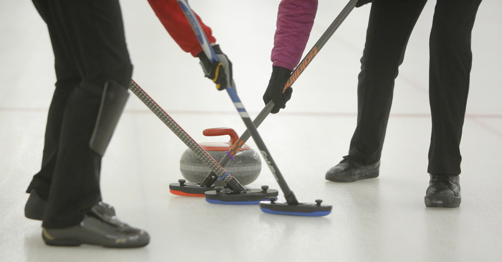 Women sweep in front of a curling stone to help it gain more distance during a curling competition at the Belfast Curling Club in Belfast on Friday, January 17, 2014.