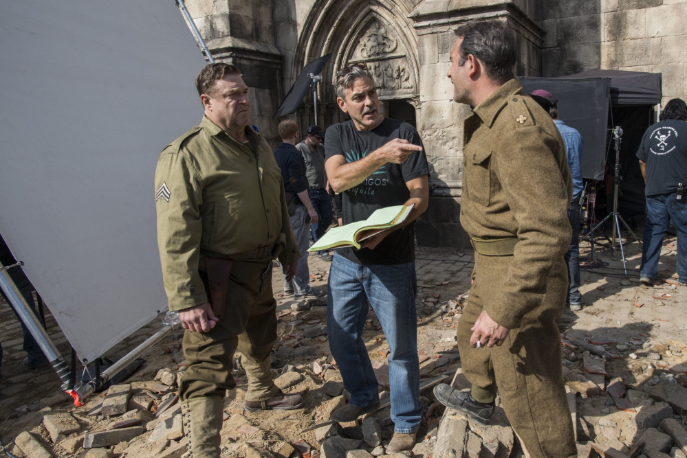 Director George Clooney, center, talks with actors John Goodman, left, and Jean Dujardin on the set of Columbia Pictures' movie