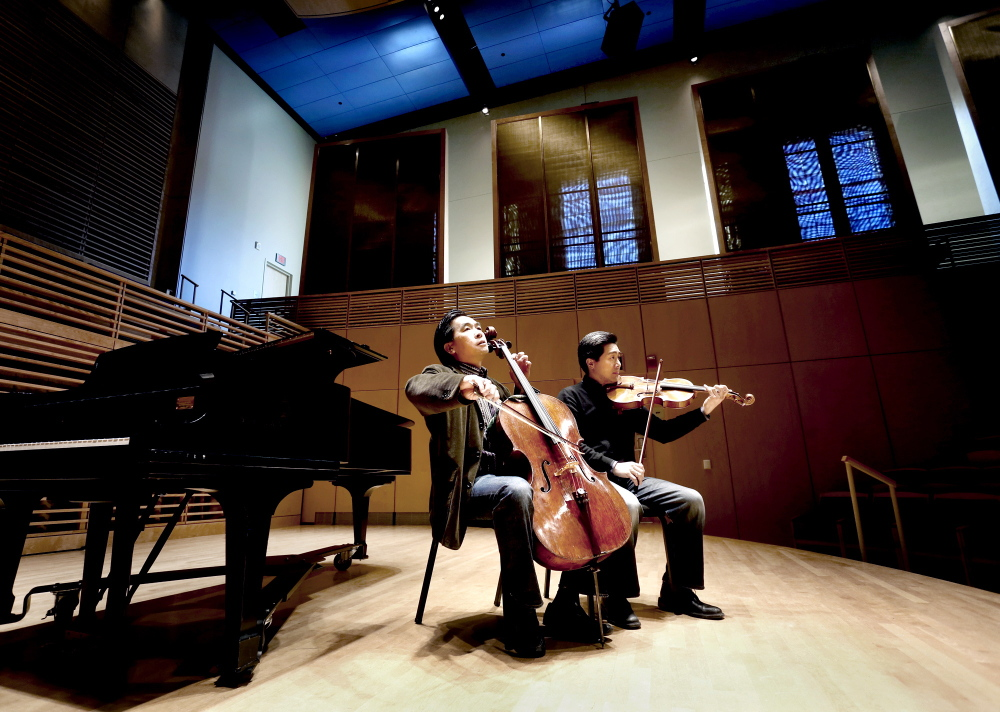 David Ying, left, plays the cello as his brother, Phillip, plays the viola in the Studzinski Recital Hall at Bowdoin College in Brunswick last week. The brothers are co-artistic directors of the upcoming Bowdoin International Music Festival.