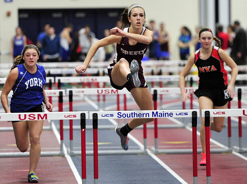 Jocelyn Mitiguy of Greely outruns the competition, including Alie Jones, left, of York and Mackenzie Sangster of North Yarmouth Academy, to win the girls' junior 55 hurdles in 9.39 seconds.