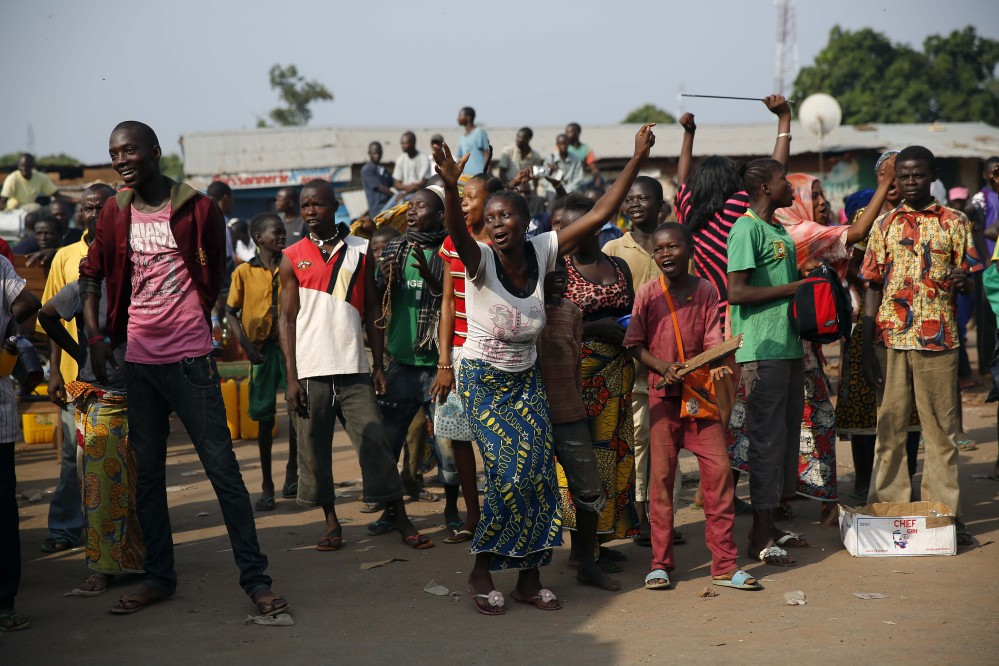 At PK12, the last checkpoint at the exit of the town, the Christian crowd cheers Friday as thousands of Muslim residents from Bangui and Mbaiki flee the Central African Republic town of Bangui, escorted by Chadian troops.