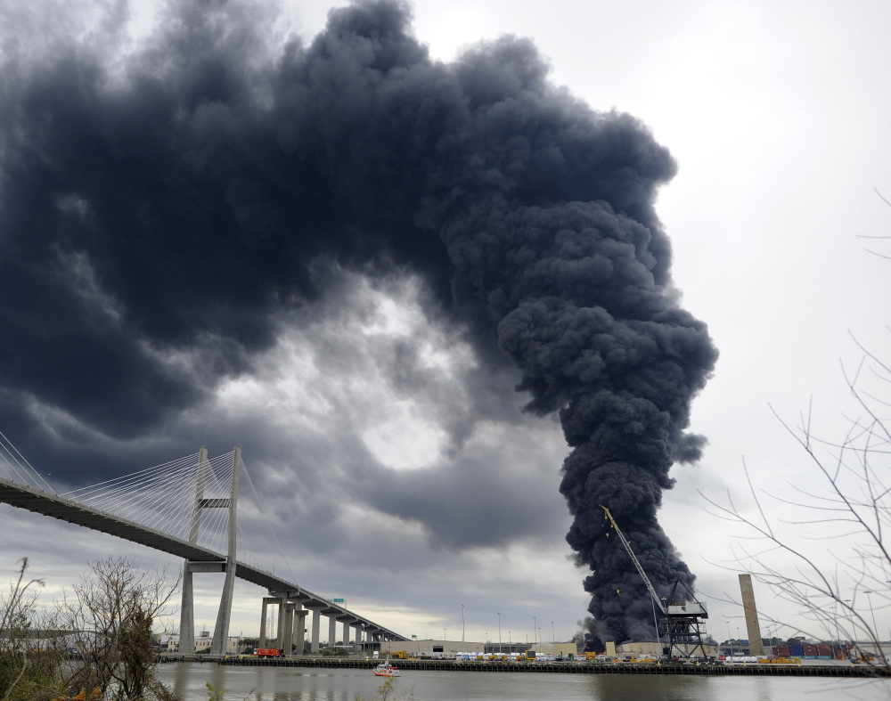 Firefighters battle a blaze in a warehouse at the Georgia Port Authority Ocean Terminal on Saturday in Savannah, Ga. Burning rubber sent up a towering column of black smoke that could be seen from miles away.