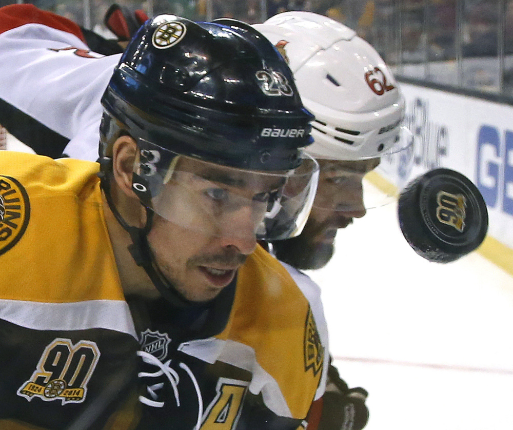 Boston Bruins center Chris Kelly, left, and defenseman Eric Gryba of the Ottawa Senators get a close look at the puck as they fight for possession along the boards during the Bruins' 7-2 win at Boston on Saturday. Patrice Bergeron led Boston with two goals and an assist.