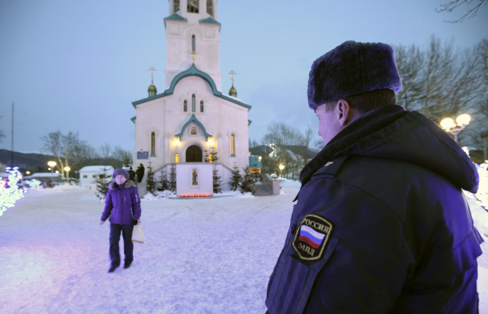 A policeman watches a believer leaving the Cathedral of the Resurrection of Christ in Yuzhno-Sakhalinsk on Sunday, Feb. 9. Law enforcement officers detained a man, who worked as a security guard, and were trying to determine why he attacked the Russian Orthodox cathedral in the city of Yuzhno-Sakhalinsk.