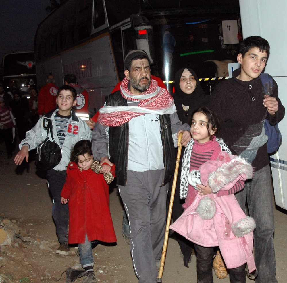 Syrians walk toward a bus to evacuate the battleground city of Homs. A Syrian Red Crescent official said around 300 more people were evacuated from the city Monday.