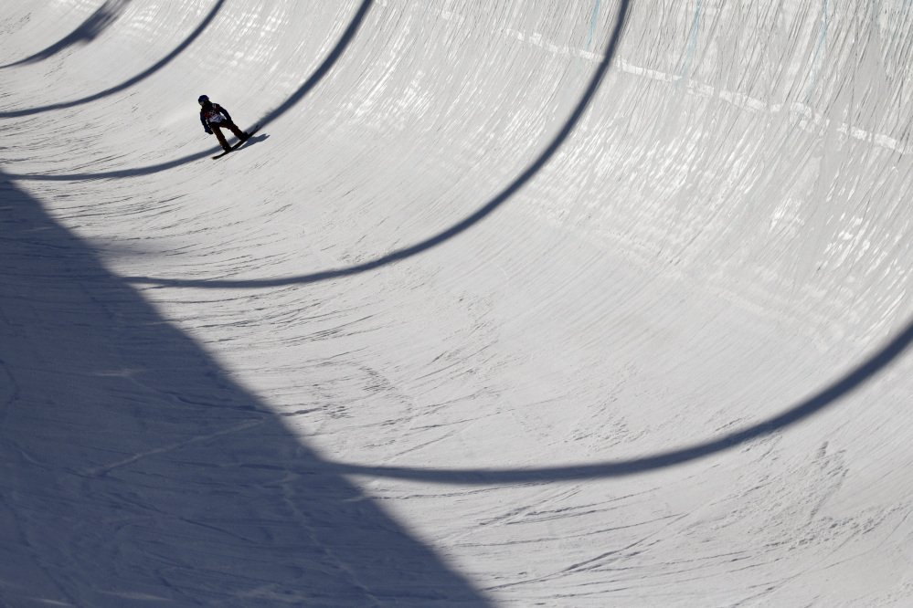 An athlete lands after a jump during a training session Saturday for the men's snowboard halfpipe at the 2014 Winter Olympics. There were dozens of falls, very few big tricks and a lot of complaining during a practice session Monday that was pushed from morning to night