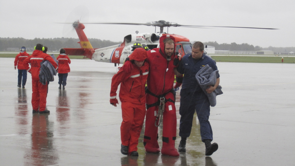 On a runway at a North Carolina air station, Coast Guard members assist one of the 14 sailors rescued after the Bounty entered the path of Hurricane Sandy and sank in 2012.