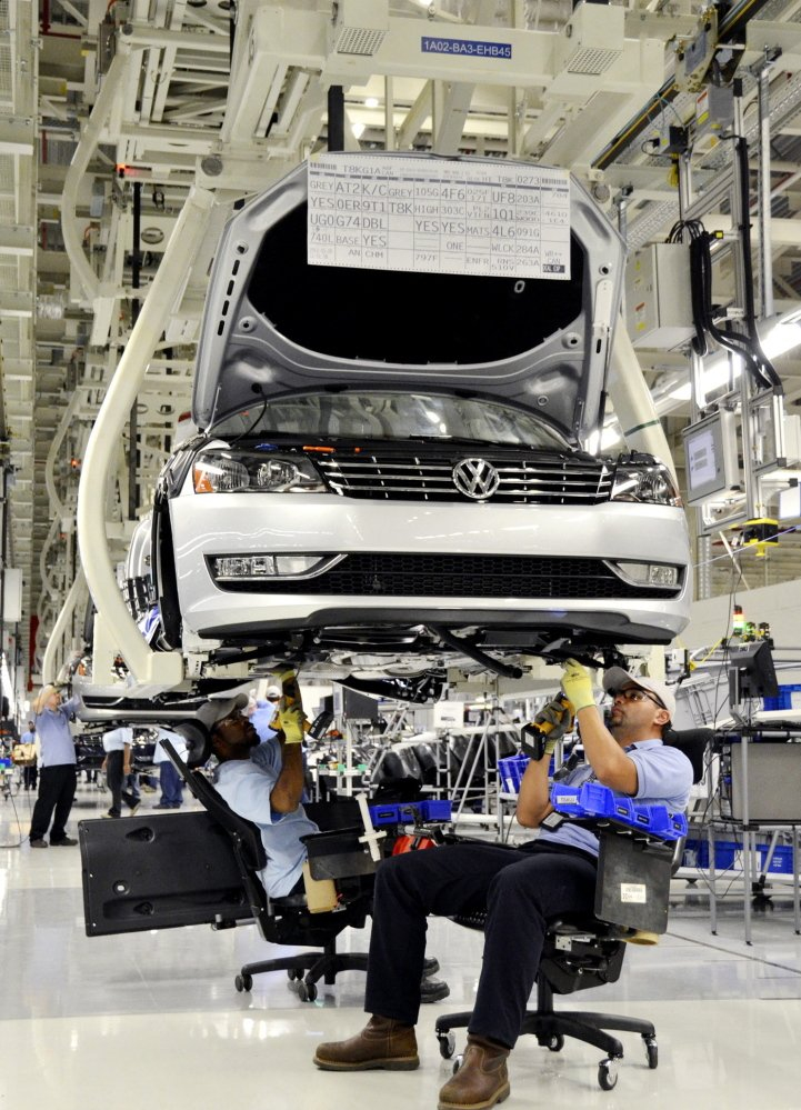 Workers in ergonomic chairs install parts on a Volkswagen Passat at the factory in Chattanooga, Tenn., in 2011. The prospect of a United Auto Workers win at the factory has officials across the South on edge.