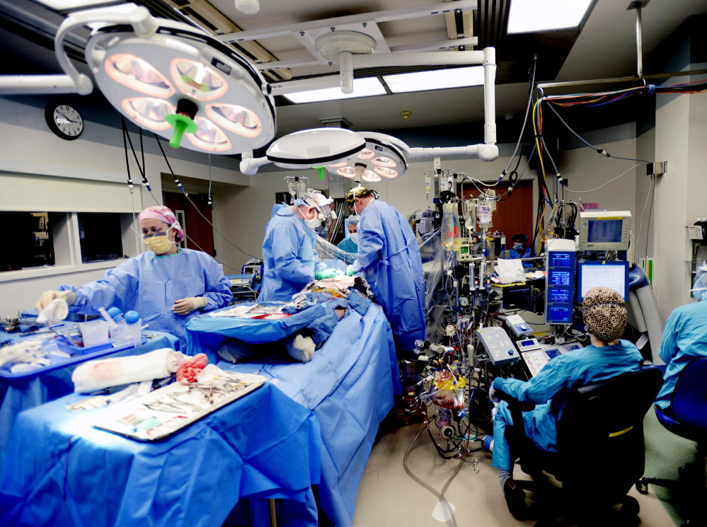 A surgery takes place in a crowded operating room at Maine Medical Center on Tuesday. Maine Med has received state approval for a $40 million expansion that will allow it to add several operating rooms.