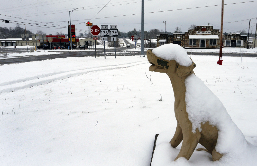Dog Town's concrete mascot is partially covered in snow Tuesday in Dog Town, Ala. A winter storm dropped from 1 inch to 3 inches of precipitation across a wide area.