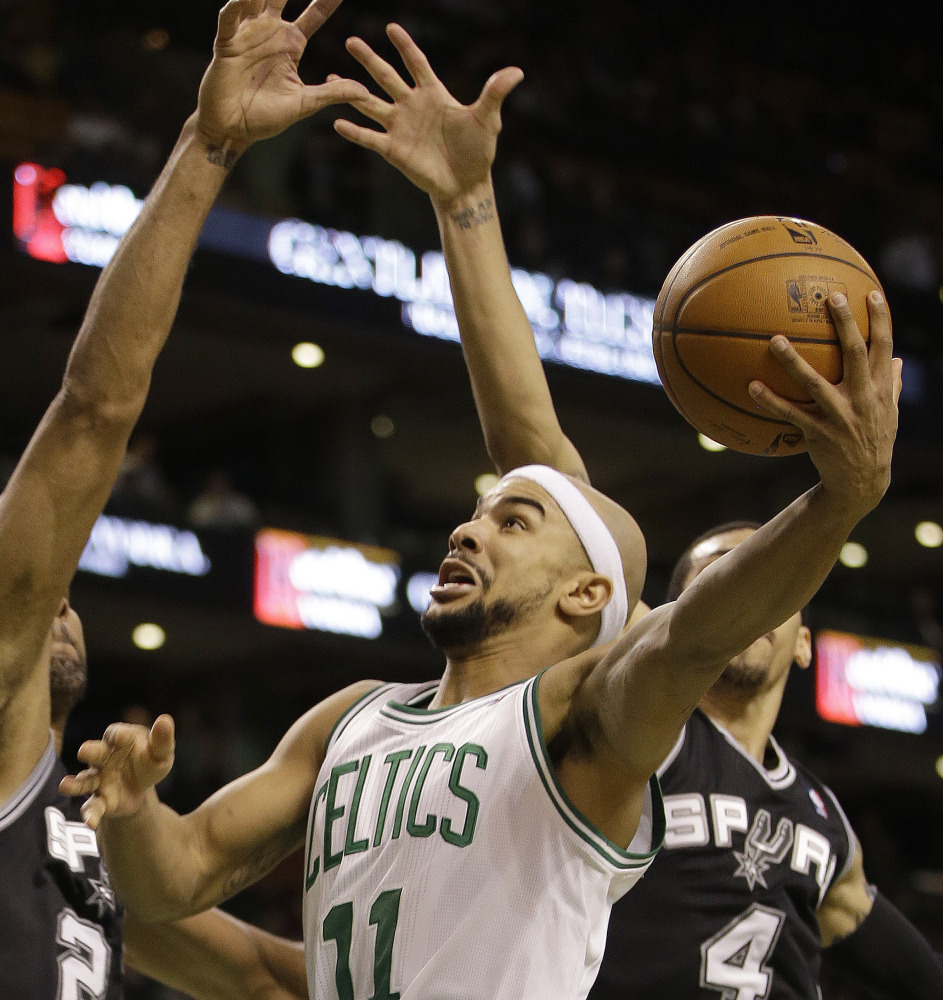 Boston Celtics guard Jerryd Bayless (11) drives to the basket against San Antonio Spurs forward Kawhi Leonard (2) and guard Danny Green (4) during the second half of an NBA basketball game in Boston, Wednesday, Feb. 12, 2014. The Spurs defeated the Celtics 104-92. (AP Photo/Stephan Savoia)